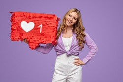 Confident young female carrying banner with like symbol and smiling for camera while advertising social media communication against violet background