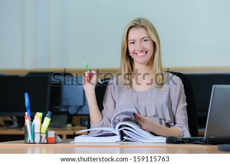 Confident young girl holding a pen, flipping a book and smiling