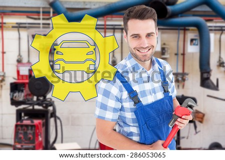Confident young male repairman holding monkey wrench against workshop