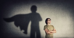 Confident young man keeps arms crossed smiling optimistic as casting a superhero with cape shadow on the wall. Motivated and ambitious guy tends to achieve success. Hero leadership and power concept