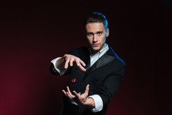 Confident young man magician showing tricks using one flying dice over dark background