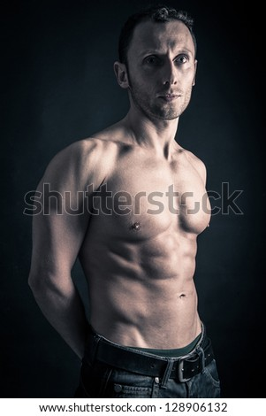Confident young man shirtless portrait against black background.