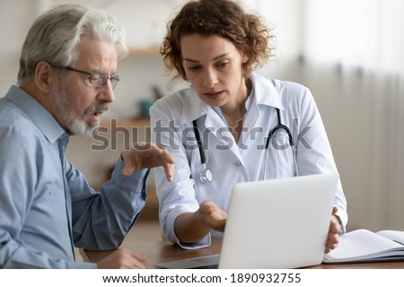Confident young 30s female general practitioner physician showing medical insurance program presentation or health lab test results on computer to focused middle aged older patient at clinic meeting.