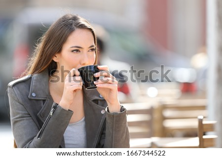 Confident young woman drinking coffee looking away sitting on a cafe terrace