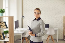 Confident young woman in eyeglasses and formal wear standing in office or classroom and holding notebook. Waist up portrait of serious school teacher, faculty member or business professional at work