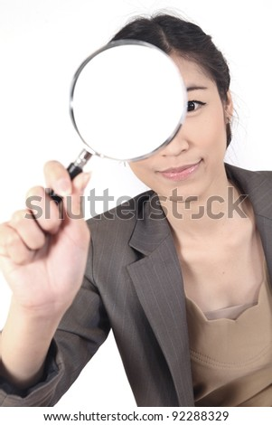 Confident young woman looking through a magnifying glass isolated (blank space for text)