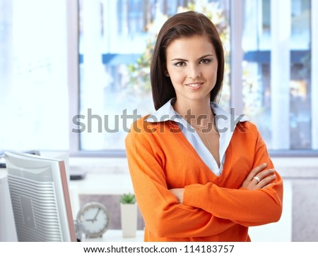 Confident young woman smiling in bright office, looking at camera.