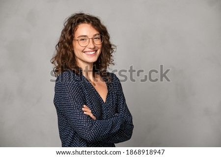 Confident young woman wearing eyeglasses and standing on gray wall. Portrait of smiling businesswoman isolated against grey background with copy space. Proud student girl with specs looking at camera.