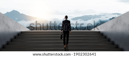 Confidential businessman in suit holding bag walk to success on stair, development and leader in business concept Stock photo ©