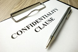 Confidentiality clause with pen on desk, business concept