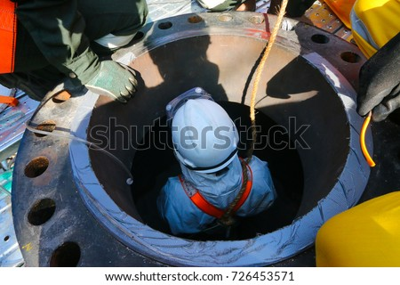 Confined space entry by a worker who wear white chemical suit.