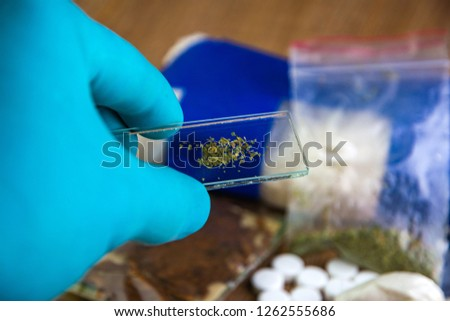confiscation of drugs -  laboratory glass with vegetable contents in the laboratory assistant's hand against the background of a lot of drugs: heroin, marijuana, amphetamines are on the table, short f