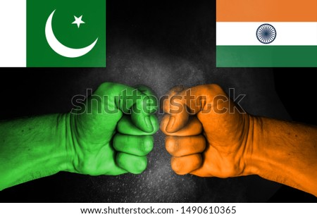 Conflict between India and Pakistan, male fists with flags painted on skin isolated on black background - governments conflict concept