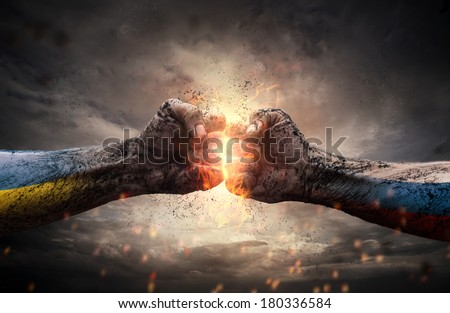 Conflict, close up of two fists hitting each other over dramatic sky