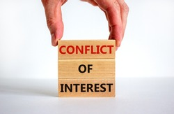 Conflict of interest symbol. Wooden blocks with words 'conflict of interest'. Beautiful white background, businessman hand. Copy space. Business and conflict of interest concept.