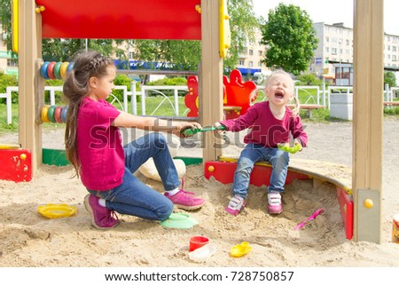 Conflict on the playground. Two sisters fighting over a toy shovel in the sandbox. Kid sister crying all throat