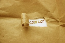 Conflict word under torn brown paper. Domestic violence. or conflict of interests Concept.