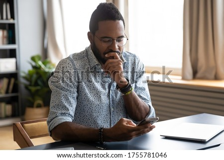 Confused African guy holding smart phone feels concerned thinking over received message. Mobile phone everyday usage, unpleasant news, waiting for important call, low signal device problems concept