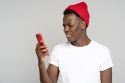 Confused African millennial hipster man looking at smartphone, annoyed by spam, intrusive adware, unpleasant message isolated on grey studio background. Black male has problem with cellphone, bad news