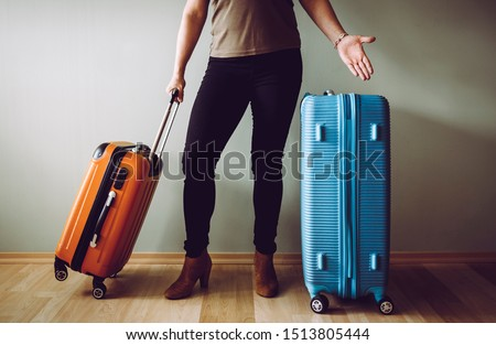 Confused and upset air passenger standing with luggage, stranded in airport. Traveling agency bankruptcy concept.