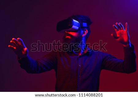 Confused bearded man in virtual reality headset. Future. Future technology concept. Men using VR headset. Virtual reality goggles. Virtual reality device. Isolated on balck background. Red and blue.