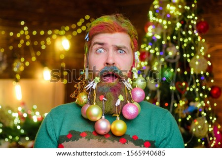 Confused bearded man with decorated beard. Christmas beard decorations. New year party. Bearded man with decorated beard. Decorated beard. Merry Christmas and happy new year. Christmas decorations.