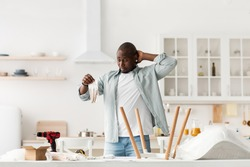 Confused black man holding package with details, collecting table with instructions, in kitchen interior, copy space. Difficult assembling of new furniture at home by yourself