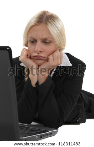 Confused blond office worker using laptop