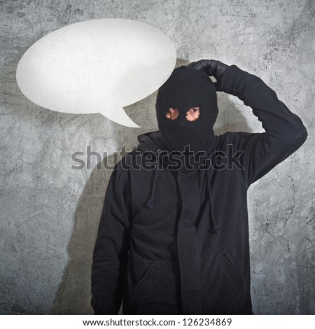 Confused burglar with speech balloon, thief with balaclava caught confused and without idea in front of the grunge concrete wall.