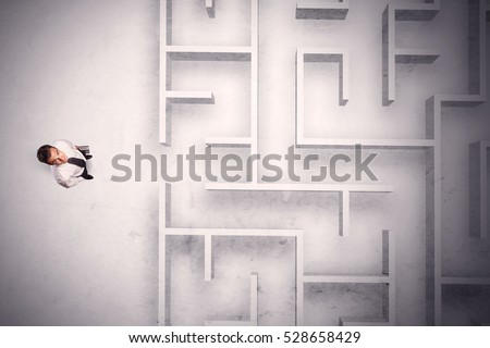 Confused businessman standing at a maze wall with grungy background