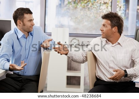 Confused businessmen sitting at desk in office, looking at each other talking.