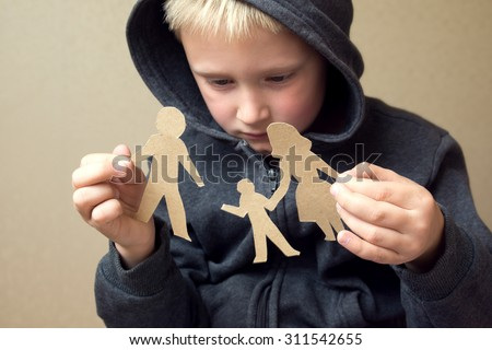 Confused child with broken paper family, family problems, divorce, custody battle, suffer concept  Stock photo ©