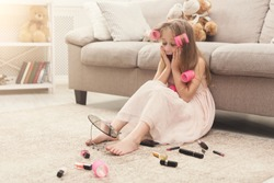 Confused cute little girl in hair curlers trying cosmetics. Pretty kid sitting on floor among lots of beauty products, looking in mirror with surprise, doing make up first time, copy space