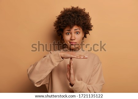 Confused dark skinned woman makes pause or break time gesture, timeout sign, wears sweatshirt, stands against brown background, asks to wait, upset about deadline. Body language concept. Time limit Stock photo ©