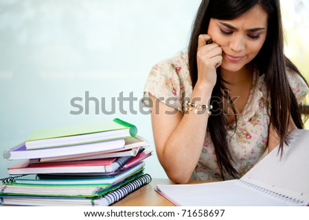 Confused female student with a pile of notebooks