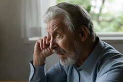 Confused frustrated old 70s aged man rubs face and eye, looks away with unhappy face. Mature elder pensioner suffers from memory loss, cataract, feels stress, lonely, despair. OAP going through grief