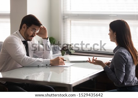 Confused male hr manager listening to female job applicant at interview. Young woman making bad first impression on doubtful company recruiter. Employer unsure about working experience of candidate.