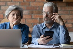 Confused mature man and woman calculate household finances expenditures, have debt problem paying bills online. Stressed senior couple manage home budget, consider paper documents. Insurance concept