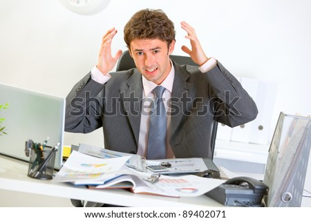 Confused modern businessman lost in documents