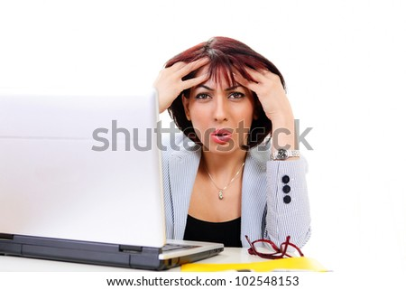 Confused office worker holding head sitting at office desk