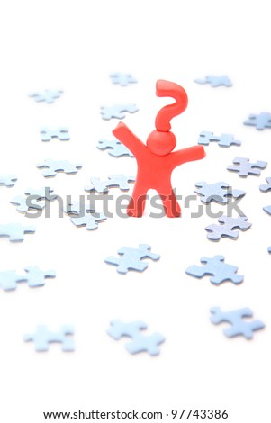 confused red plasticine guy with question mark on his head standing between lots of unsolved jigsaw puzzle pieces - isolated on white