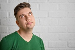Confused rolls his eyes up, hands folded on his chest. Portrait of a handsome caucasian man. Brick wall background. Studio photo.