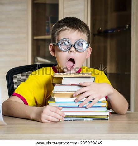 Confused schoolboy in funny glasses screaming near the huge stack of books. Education.