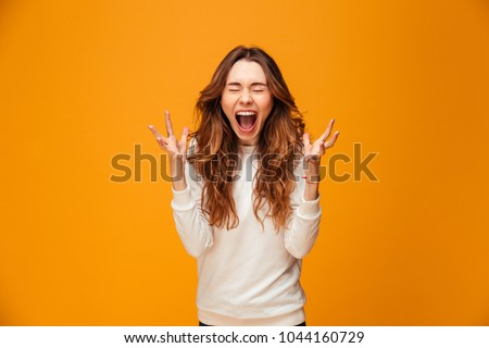 Confused screaming brunette woman in sweater with closed eyes over yellow background #1044160729