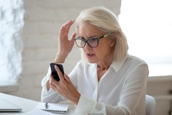 Confused senior businesswoman sit at office desk hold cellphone experience internet connection problem, frustrated aged woman worker feel disappointed having smartphone breakdown or virus attack