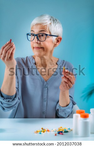 Confused senior woman looking at her medicines on the table. Medicine non-adherence concept. Stock photo ©