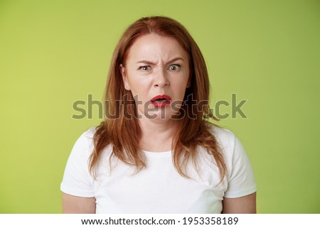 Confused shocked gasping middle-aged redhead woman cringe frustrated puzzled open mouth speechless freak out strange shocking scene stand green background perplexed disappointed Stockfoto ©