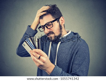 Confused stressed man looking at too many credit cards full of debt