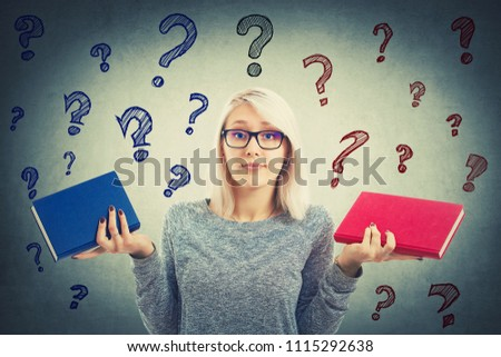 Confused student girl choosing between two books, red and blue, left or right which one to read. Difficult decision, education concept, making the correct choice and question marks flying above head.