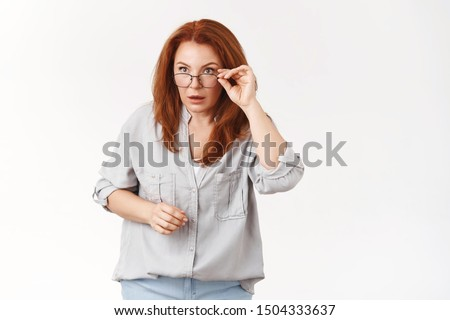 Confused stunned speechless redhead middle-aged woman taking off glasses stare sideways astonished puzzled cannot understand what going on strange things happen standing perplexed white wall
